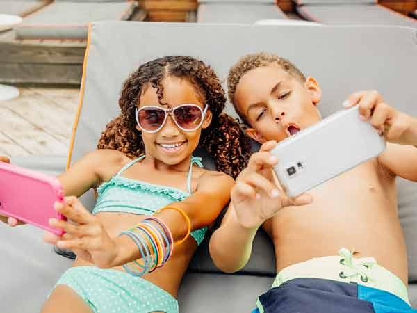 Kids taking selfies, at Sunny Isles Beach